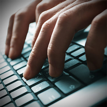 Image of hands typing on a laptop keyboard